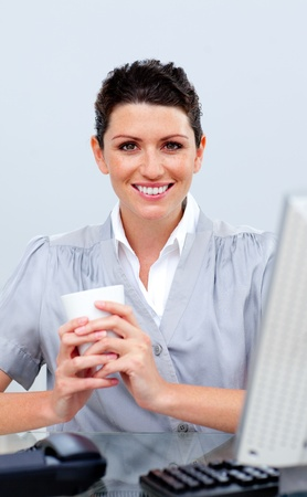 Positive business woman drinking coffee photo