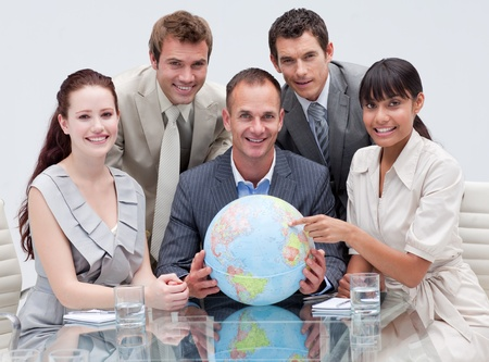 businessmeeting: Smiling business team holding a terrestrial globe