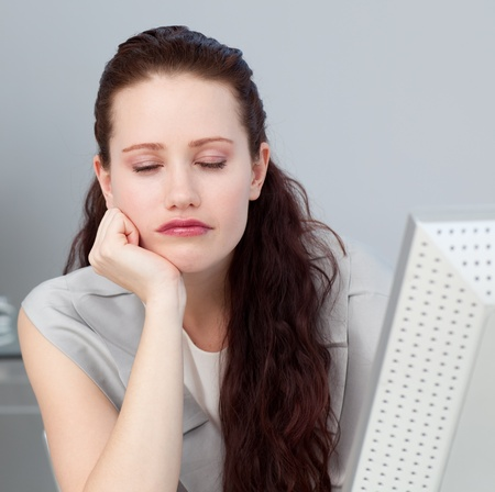 Close-up of a bored businesswoman sleeping at her desk photo