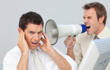 berisping: Zakenman schreeuwen door een megafoon bij zijn collega Stockfoto