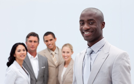 Smiling Afro-American businessman in front of his team photo