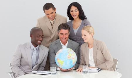 businessmeeting: Multi-ethnic business team holding a terrestrial globe