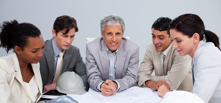 Architect manager in a meeting with his team studying plans photo