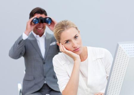 afflict: Blond businesswoman annoyed by a man looking through binoculars