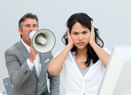 Competitive businessman shouting through a megaphone photo