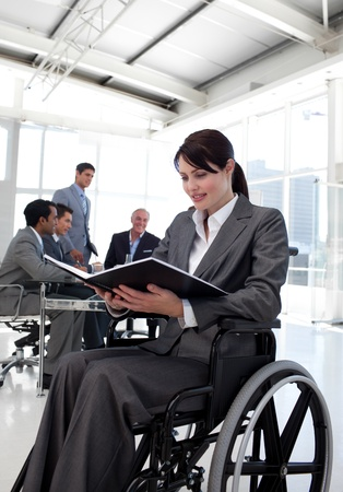 handicapped accessible: Businesswoman in a wheelchair reading a report