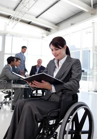 handicap: Imprenditrice in una sedia a rotelle la lettura di un rapporto