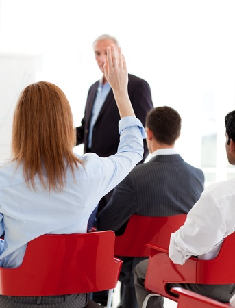 Businesswoman raising her hand up at a conference Stock Photo - 10218773