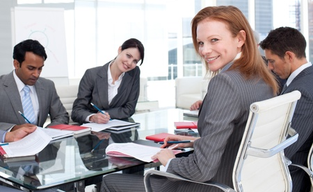 Smiling businesswoman in a meeting with her team photo
