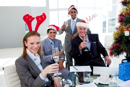 Multi-ethnic busioness team toasting with Champagne at a Christmas party photo