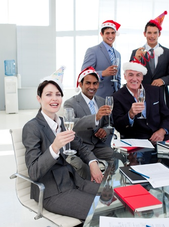 Manager and his team with novelty Christmas hat toasting at a party photo