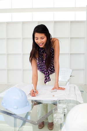 Portrait of a female architect studying plans photo