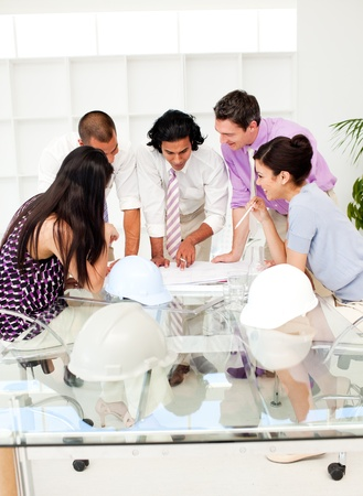 engineering design: A team of architects at the meeting looking at blueprints Stock Photo