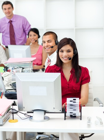 Smiling business people with headset on working  photo
