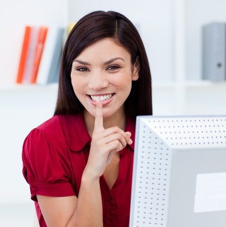 quiet adult: Close-up of a smiling businesswoman askig for silence