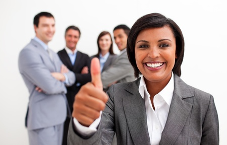 Attractive female executive smiling at the camera with thumb up photo