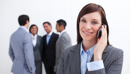 talking by phone: Attraente manager del telefono con il suo team in background