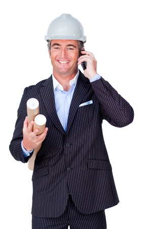 Smiling businessman on phone and holding blueprints photo
