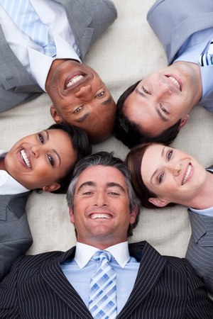 Smiling business team lying on the floor with heads together Stock Photo - 10216912