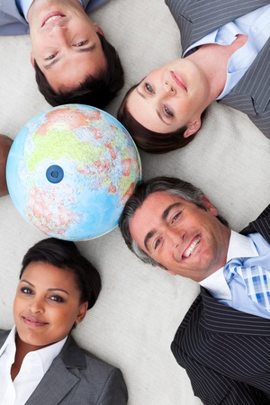 businessmeeting: Multi-ethnic business team lying on the floor around a terrestrial globe  Stock Photo