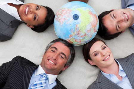businessmeeting: Business people lying on the floor around a terrestrial globe
