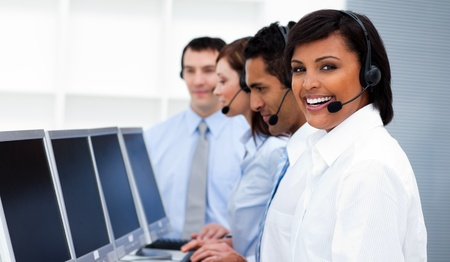 computer support: Happy co-workers with headsets on working in call center Stock Photo
