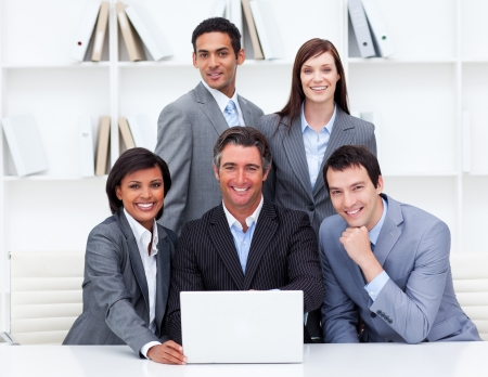 teaming: Successful business team looking at a laptop Stock Photo
