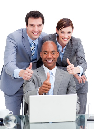 Diverse business co-workers with thums up at a laptop photo