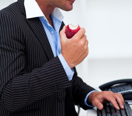 business dinner: Close-up of a businessman eating a fruit Stock Photo
