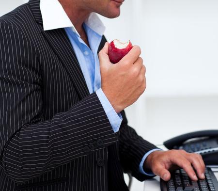 tentempi�: Primer plano de un hombre de negocios comer una fruta Foto de archivo