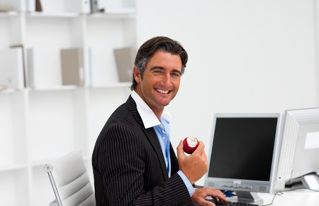 Businessman eating a fruit at work  photo