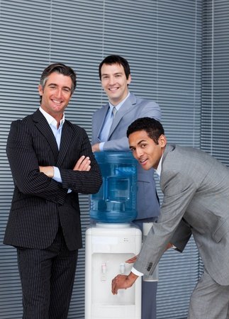 Portrait of a business team filling cup from water cooler photo