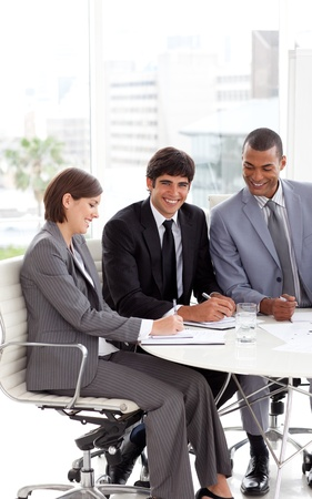 Young business people sitting at a conference table photo