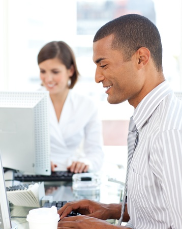 Two positive colleagues working at a their computer photo