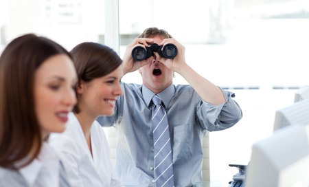 Charismatic businessman looking through binoculars photo
