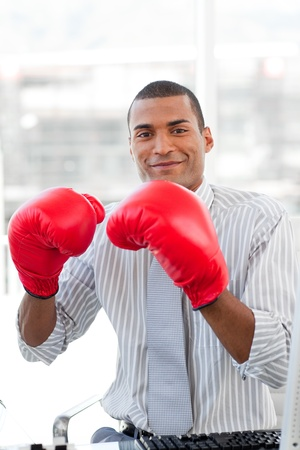 Successful businessman beating the competion with boxing gloves  photo