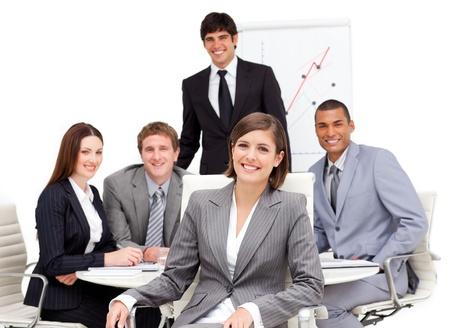 キャリア: 彼女のチームの前に座って魅力的な女性実業家 写真素材