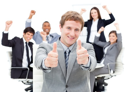 Happy manager with thumbs up in front of his team photo