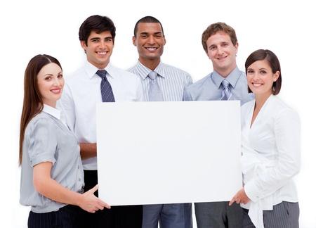 L�chelnd internationale Gesch�ftsleute halten eine wei�e Karte Stockfoto