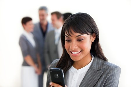 Smiling businesswoman sending a text in front of her team Stock Photo - 10259554