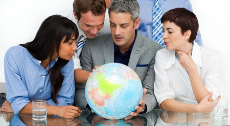 businessmeeting: International business people looking at a terrestrial globe  Stock Photo
