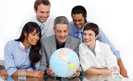 businessmeeting: Smiling multi-ethnic business partners holding a globe