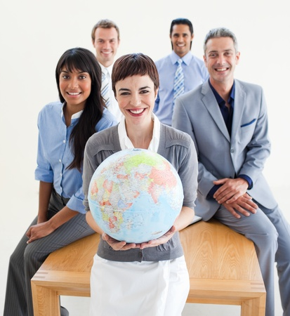 Cheerful multi-ethnic business people holding a terrestrial globe  Stock Photo