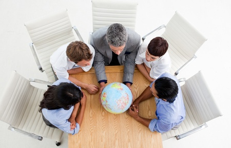 Confident business people around a terrestrial globe photo