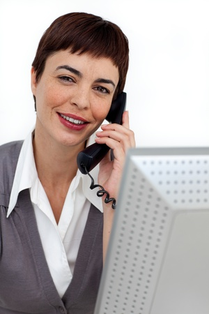 Assertive Businesswoman on phone at her desk Stock Photo - 10258599