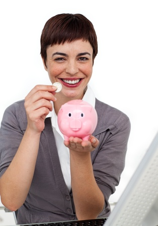Joyful Female executive saving money in a piggybank photo