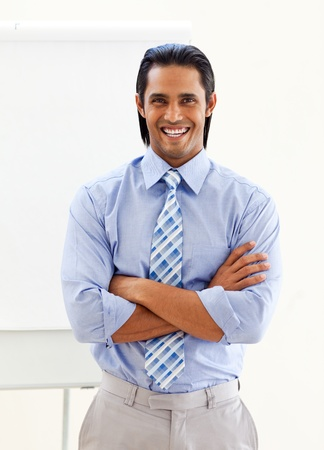 Cheerful ethnic businessman in front of a board  photo