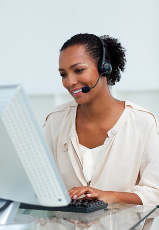 Cheerful businesswoman with headset on working at a computer photo