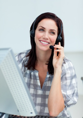 Radiant businesswoman with headset on working at a computer  photo