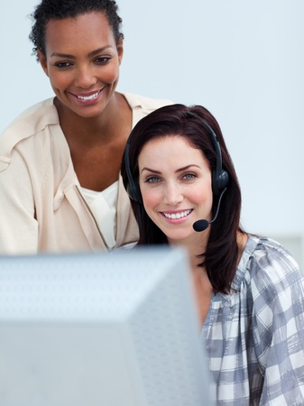 Smiling business partners working at a computer  photo